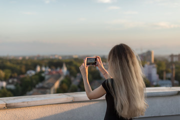 Girl taking photos from the roof at sunset