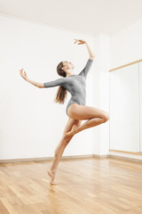 Young beautiful female  ballett dancer posing in studio
