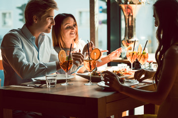 Young beautiful woman smiling while eating fresh and tasty seafood during lunch with her best friends at the restaurant