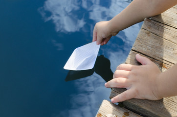 Hands of little boy, releases into the water paper boat with wooden pier.