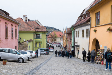 Tourists walk on the School Street in the castle of old city. Sighisoara city in Romania