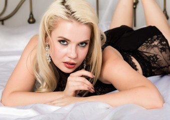 sensual sexy woman resting on a bed in hotel room. Blonde wearing in seductive black lingerie