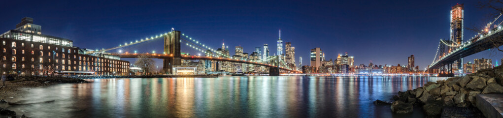 Fotomurales - The skyscrapers of Lower Manhattan, the Brooklyn Bridge and the Manhattan Bridge in evening with the East River (panoramic). New York City