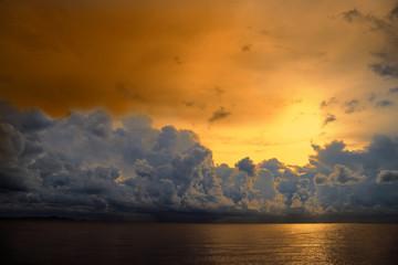 sunset sky over silhouette orange heap cloud on sea