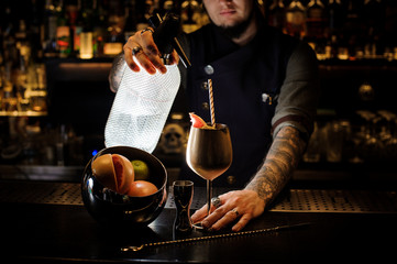 Bartender with tattoo pouring soda into the copper cocktail glass