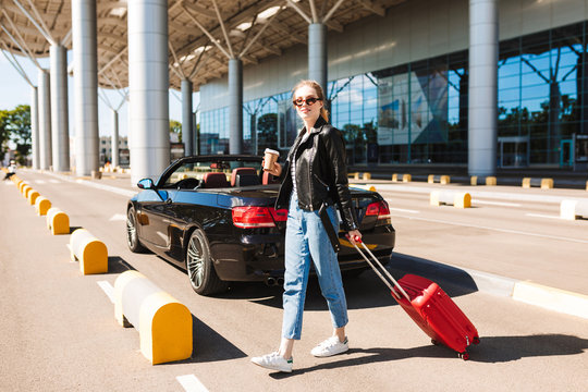 Beautiful girl in sunglasses and leather jacket dreamily looking in camera holding coffee to go and red suitcase near airport with cabriolet on background