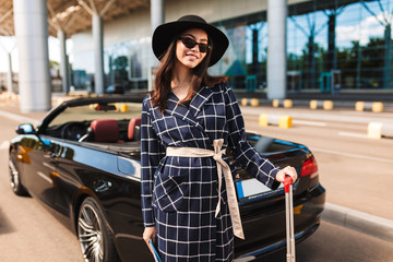 Pretty smiling girl in sunglasses and black hat happily looking in camera near airport with cabriolet on background