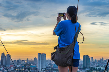 girl capture cityscape by smartphone on rooftop