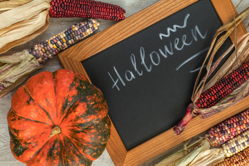Holiday Halloween background with indian multicolored corn, pumpkin and slate blackboard