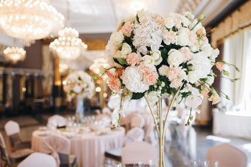 Pink and white wedding bouquet stands in the middle of dinner table