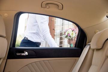 Groom opening the door to his bride