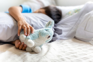 Little boy sleeping in bed and holding his bunny robbit.