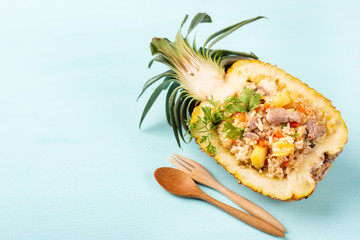 Fried rice with pork in half pineapple fruit on green background, Thai cuisine