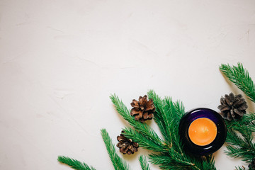 Christmas background with fir tree and decor, cones and candle. Top view with copy space, white background