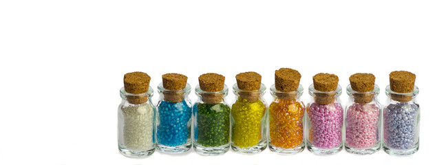 Little bottles in a row with colorful beads isolated on a white background, banner for facebook