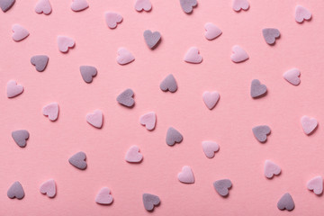 beautiful sweet pink sprinkles of heart shapes over pink background, concept of St. Valentines Day