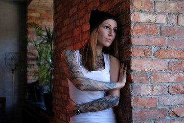 Portrait of a blonde tattoed girl dressed in white t-shirt and hat leaning on a brick wall in room with loft interior.