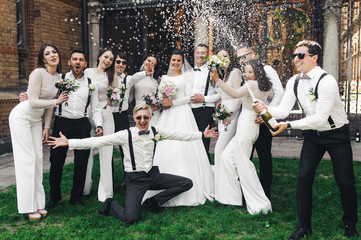 Newlyweds and friends open a bottle of champagne posing on the green lawn