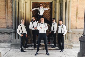 Groom and groomsmen in black trousers pose between columns