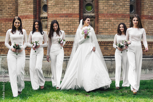 Beautiful Bride And Bridesmaids With Wedding Bouquets Pose On The