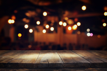 Image of wooden table in front of abstract blurred restaurant lights background. Fotomurales