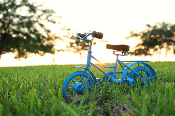 Blue vintage bicycle toy waiting outdoors at sunset light.
