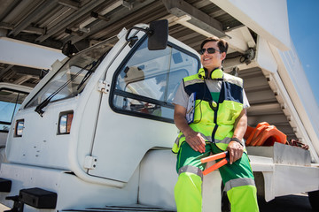 Feeling comfortable. Low angle portrait of cheerful aviation marshaller sitting on vehicle. Man holding signal wands and looking away
