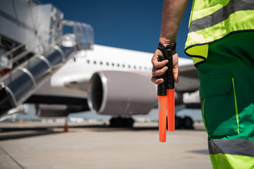 Heading to aircraft. Close up of airport worker arm with marshalling wands. Runway and passenger plane on blurred background