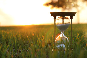 Hourglass in the grass time during sunset. vintage style. Wall mural