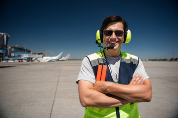 Time for fun at work. Waist up portrait of smiling man in headphones with vignette effect. Blue sky, terminal, runway and planes on background