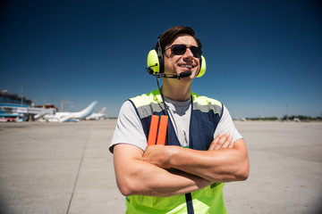 Enjoying beautiful sunny day. Waist up portrait of smiling man in headphones and sunglasses. Blue sky, runway and planes on background
