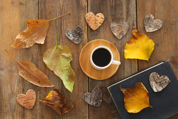 top view image of coffee cup over wooden , dry autumn leaves and stack of book.
