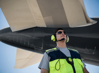 Looking up. Low angle portrait of serene man in sunglasses posing at airport. Blue sky and aircraft tail on background