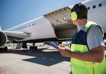 Fototapeta Aircraft ground handling. Man in headphones observing airplane with open cargo door and intending to fill out documents. Copy space in left side