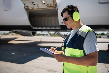 Important data. Side view of serene man in sunglasses and headphones filling out documents. Plane with open cargo door in the background