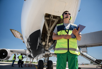Preparation for the flight. Low angle portrait of man in sunglasses holding documents and posing near aircraft with open door. Ground crewmembers standing behind