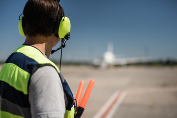 Soft landing. Back view of airport worker holding signal wands. Passenger aircraft and runway on blurred background