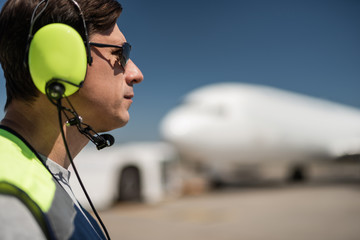 Great profile. Close up of serious man in sunglasses and headphones at airdrome. Copy space in right side