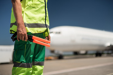 Work outfit. Close up of male arm holding sticks for signaling. Passenger plane and runway on blurred background