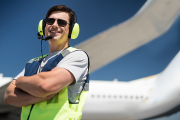 Nice shot. Low angle portrait of ground crew member smiling and posing near passenger plane. Copy space in right side