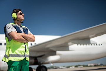 Looking at the sky. Side view of airport worker with passenger plane on blurred background. Man is pursing lips