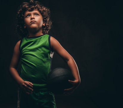 Little basketball player in sportswear holding ball in a studio. Isolated on the dark textured background.