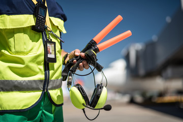Waiting for plane. Close up of airport worker torso in vest and arm with headset. Airdrome on blurred background