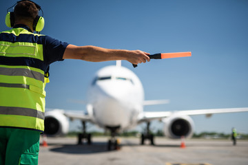 Important signal. Back view of airport worker meeting aircraft and showing right position for landing Fototapete