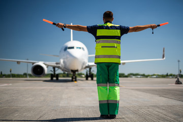 Welcome back. Back view of airport worker looking at passenger plane and signaling