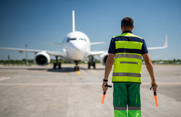 Welcome back. Back view of airport worker meeting passenger aircraft