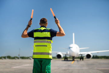 Signaling for you. Back view of aviation marshaller meeting airplane