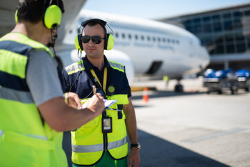 Right here. Smiling man in headphones pointing at clipboard while partner looking at writing data. Passenger plane on blurred background