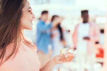 Side view optimistic young lady with attractive smile tasting appetizing beverage during rest
