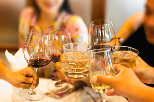 Group of friends raising a toast with glasses of red wine and whiskey at family dinner.